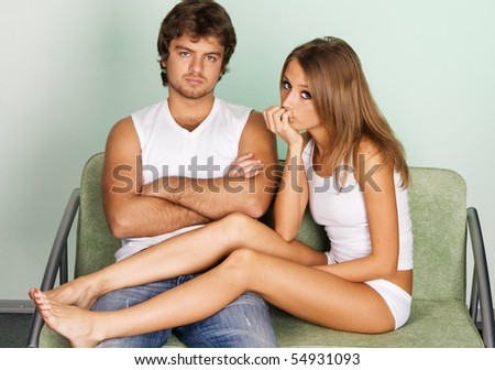 Young couple sitting on green sofa - stock photo