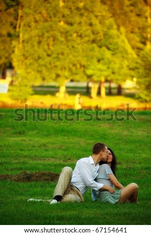 young couple sitting on park lawn and embrace - stock photo