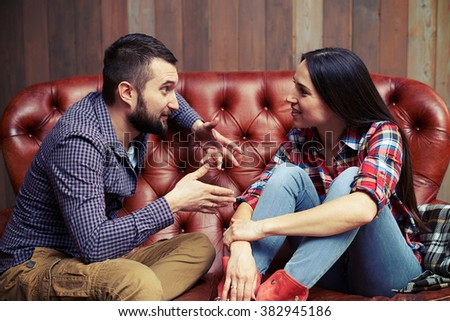 young couple sitting on sofa and have a interesting conversation - stock photo