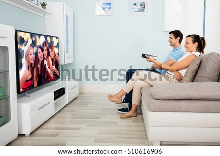 Young Couple Sitting On Sofa In Front Of Television Watching Movie At Home