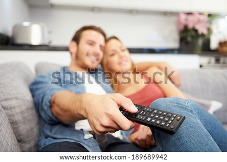Young Couple Sitting On Sofa Watching Television - stock photo