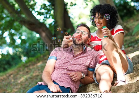 Young couple sitting on stairs in the park and blowing bubbles. - stock photo