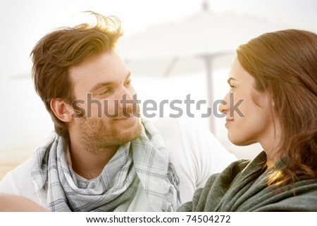 Young couple sitting on summer beach with blanket enjoying sunset, looking at each other, smiling.? - stock photo