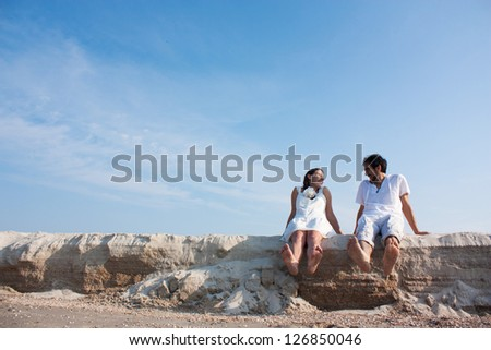 young couple sitting on the beach and laughing - stock photo