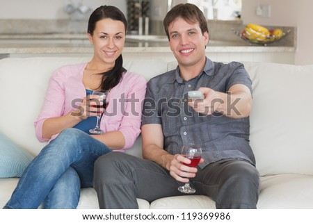 Young couple sitting on the couch in the living room while watching television - stock photo