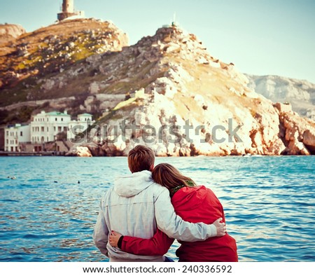 young couple sitting on the dock - stock photo