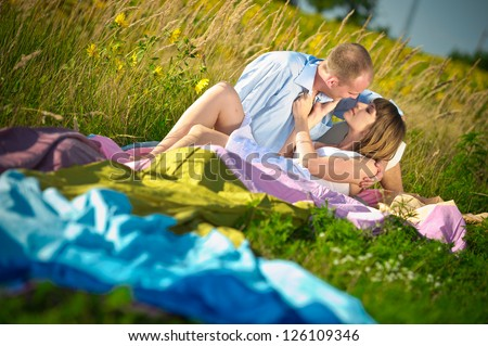 young couple sitting on the field - stock photo
