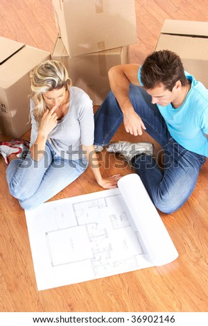 young couple sitting on the floor and looking at blueprints. - stock photo