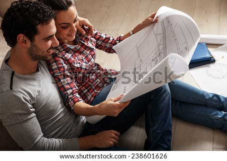 Young couple sitting on the floor and looking at the blueprint of new home. - stock photo