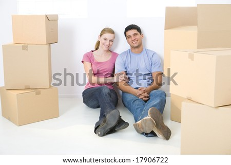 Young couple sitting on the floor between cardboard boxes. They're looking at camera. Front view.