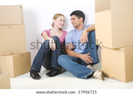 Young couple sitting on the floor between cardboard boxes. They're looking at each other's. Front view.