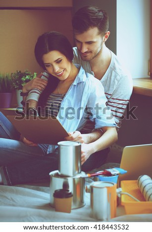 Young couple  sitting on the floor of their new apartment - stock photo