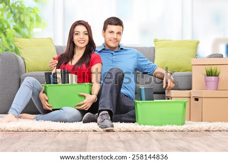 Young couple sitting on the floor with moving boxes full of their stuff at home - stock photo