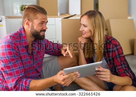 Young couple sitting on the floor with tablet pc and choosing furniture to their new apartment