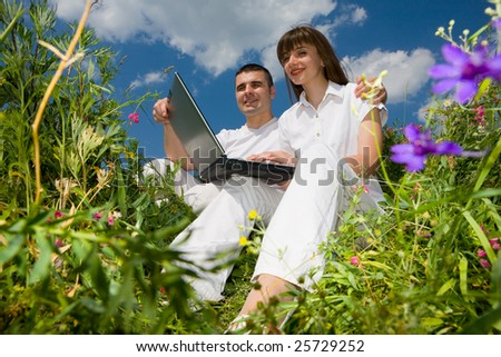 Young couple sitting on the grass field with a laptop - stock photo