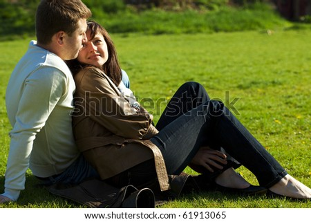 young couple sitting on the green grass - stock photo