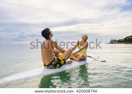 Young couple sitting on the paddle board near the beach and enjoing sunset - stock photo