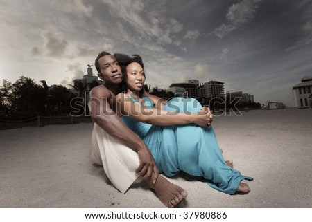 Young couple sitting on the sand - stock photo