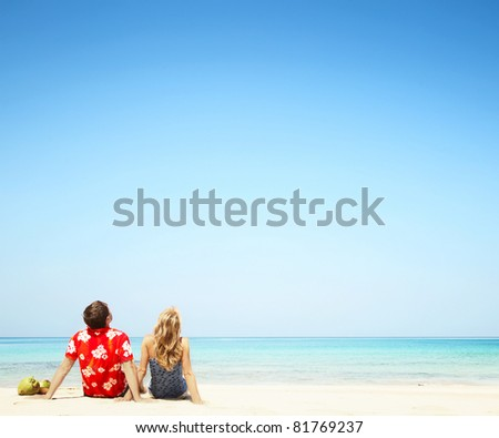 Young couple sitting on yellow sand by blue sea and looking to a clear sky