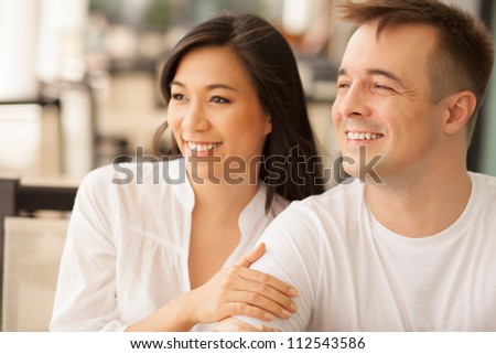 Young couple sitting together and looking away - stock photo