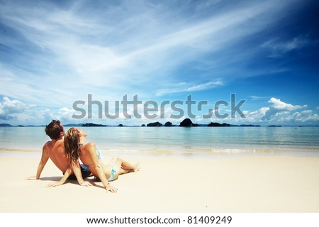 Young couple sitting together on a sand by sea and looking to a horizon - stock photo