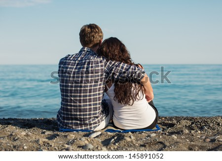 Young couple sitting together on beach  - stock photo