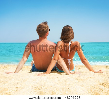 Young Couple Sitting together on the Beach. Sand by Sea. Travel and Vacation concept. Young Family Relaxing and Enjoying their Summer Holiday - stock photo