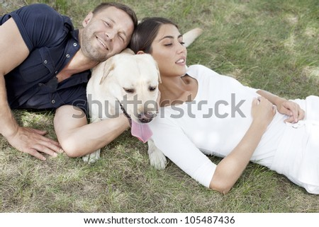 Young Couple sitting with Dog - stock photo