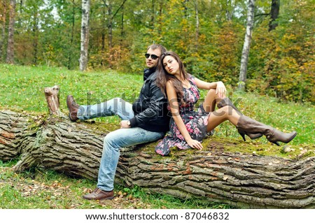 young couple sitting with his back against the trunk of the tree - stock photo