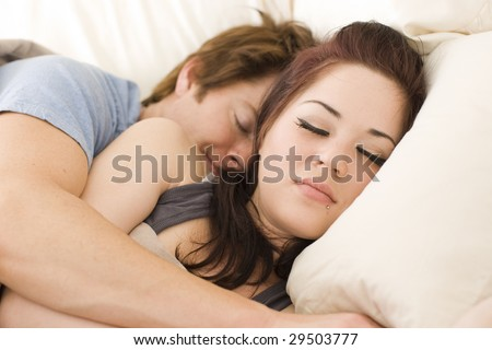 Young couple sleeping in bed - stock photo