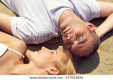 Young couple sleeping on sand in nature