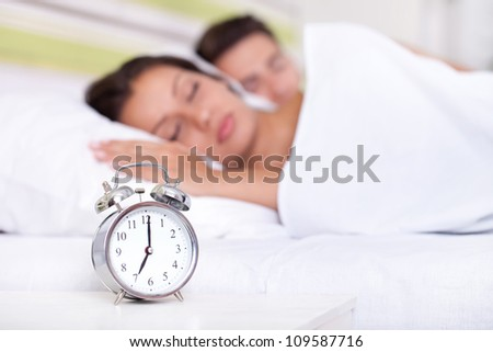 Young couple sleeping together in bed with  alarm clock