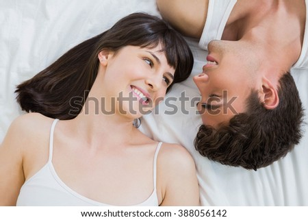 young couple smiling and lying on bed in bedroom