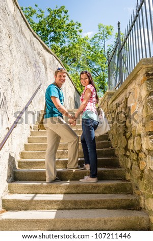 Young couple smiling holding hands on stairs romantic portrait - stock photo