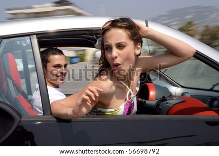 Young couple smiling in a car - stock photo