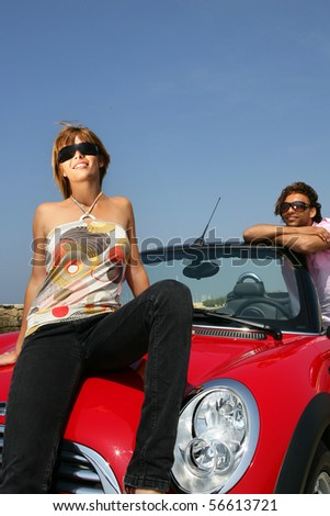 Young couple smiling leaning on a car - stock photo