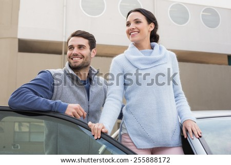 Young couple smiling together outside their car - stock photo