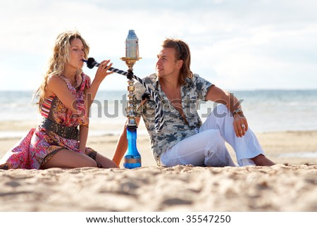 Young couple smoking hookah on a beach - stock photo