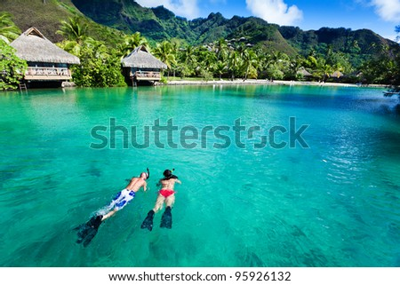 Young couple snorkeling in clean water over coral reef - stock photo