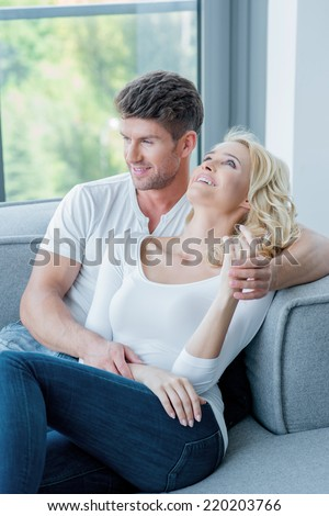 Young couple spending a relaxing day at home reclining together on a sofa below a window overlooking the garden looking off to the side with a smile - stock photo