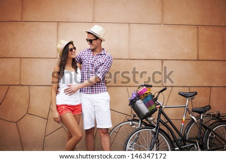 Young couple standing against the wall and hugging - stock photo