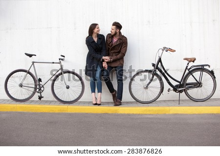 Young couple standing against the wall and hugging in city. two bikes stand next - stock photo