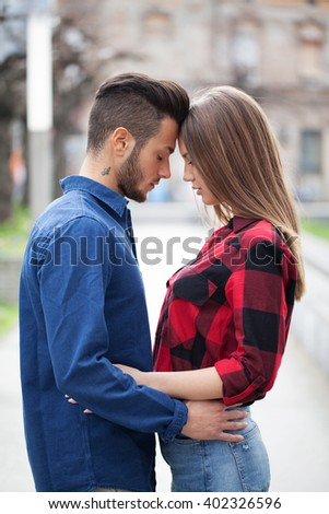 Young couple standing and hugging - stock photo