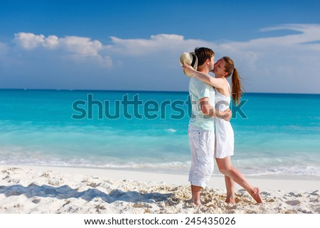 Young couple standing at beach during summer vacation - stock photo