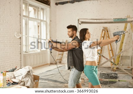 Young couple standing back-to-back, using power drill, renovating home. - stock photo