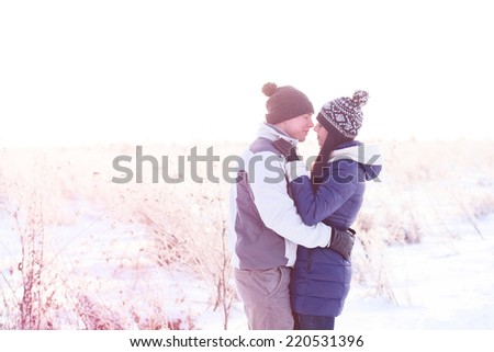 Young couple standing in a winter forest - stock photo