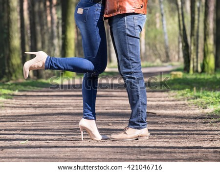 Young couple standing  in spring park and girl bending her leg - stock photo