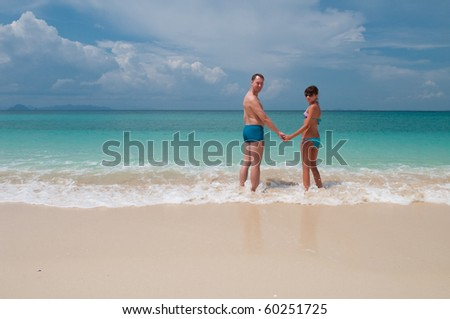 Young couple standing on a sandy tropical beach