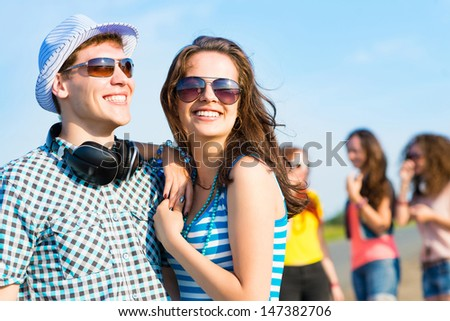 young couple standing on the road, having fun with friends - stock photo