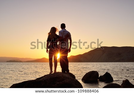 Young couple standing on the shore in the arms and looks at the setting sun by the sea - stock photo
